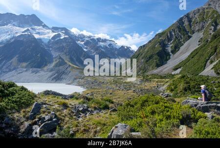 Man on Rock mit Gletschern und schneebedeckten Bergen und See, Aoraki/Mount Cook National Park, South Island, Neuseeland
