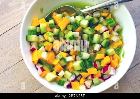 Schüssel mit frischem Salsa mit Mango, Rettich, Gurke und Tomatillo - Stockfoto