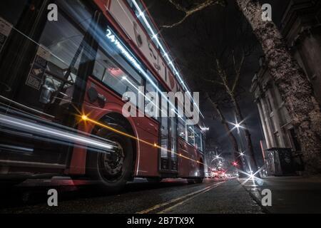 Ein Langzeitbild eines Londoner Busses, der an einer Bushaltestelle in der Charing Cross Road ankommt. - Stockfoto