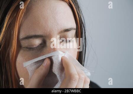 Niesen, Husten oder Blasen der Nase in einem einzigen Papiertowl. Das Konzept, Kälte, Viren oder Infektionen zu fangen und nicht zu verbreiten - Stockfoto