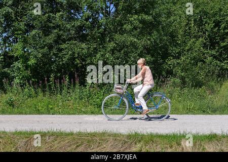 Eine ältere Frau, die mit dem Fahrrad auf einer Straße unterwegs ist, Boda Kyrkby, Rattvik, Dalarna - Stockfoto