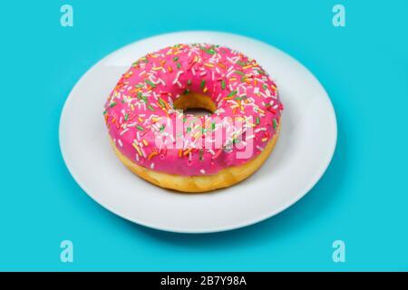 Bunte holey Donut Kuchen mit rosafarbener Glasur auf weißem Teller und türkisblauem Hintergrund. Isoliertes Bild. - Stockfoto