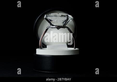 Nahaufnahme eines Diamantrings in einem Kasten unter den Lichtern vor schwarzem Hintergrund - Stockfoto