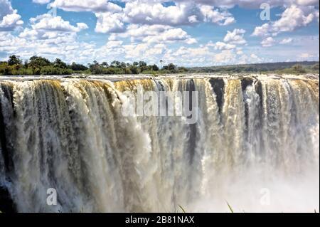 Die majestätischen Victoria Falls in voller Hochwasserperiode im April am Ende der Regenzeit - Stockfoto
