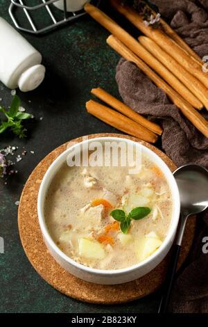 Das Konzept eines gesunden und diätetisch zubereiten Essens, leckere Suppe mit Huhn, Frischkäse und Müsli auf einem dunklen Steintisch. Kopierbereich. - Stockfoto