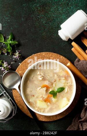 Das Konzept eines gesunden und diätetisch zubereiten Essens, leckere Suppe mit Huhn, Frischkäse und Müsli auf einem dunklen Steintisch. Flacher Laienhintergrund in der Draufsicht. SP kopieren - Stockfoto