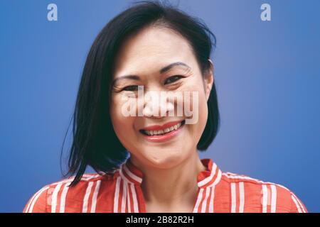 Senior-Asian-Frauen-Porträt vor blauem Hintergrund - lächelnde chinesische Frau hat Spaß, sich vor der Kamera zu posieren - reifes People Lifestyle-Konzept - Stockfoto