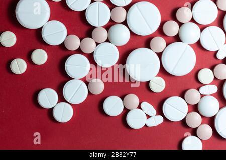 Haufen weißer Pillen, Tabletten, Kapseln auf rotem Hintergrund. Medikamentenverordnung für die Behandlung Medikation Gesundheitskonzept WTH-Kopierraum - Stockfoto