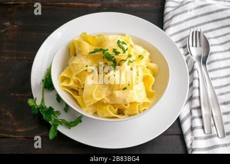 Pappardelle al Limone: Eine Schüssel mit breiten Nudeln in einer cremigen Zitronen-Parmesan-Sauce - Stockfoto