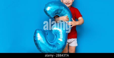 Kleiner süßer blonder Junge auf blauem Hintergrund mit Folienbeschichtung in baloonblauer Farbe. Alles gute zum Geburtstag drei Jahre alt - Stockfoto