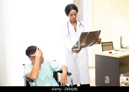 Ein männlicher Patient saß wegen Kopfschmerzen auf dem Rollstuhl. Im Krankenhaus behandelt und von einem Arzt überwacht. - Stockfoto
