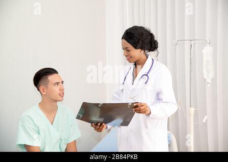 Ein männlicher Patient saß auf dem Bett. Unter Behandlung und unter Aufsicht eines Arztes, in dem der Arzt die Ergebnisse des Röntgenfilms untersucht. - Stockfoto
