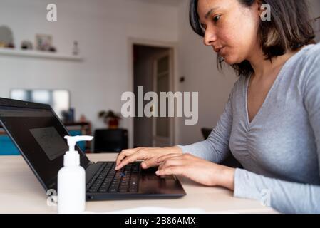 Junge Frau, die wegen des Ausbruchs des Corona-Virus eine Gesichtsmaske trägt und mit Händedededesinfektionsmittel vom Home Office aus arbeitet, ist Quarantäne eine Maßnahme, die bis zu s durchgeführt wird - Stockfoto