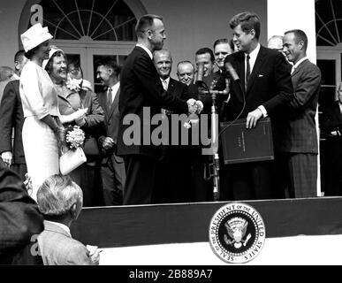 Präsident John F. Kennedy gratuliert Astronaut Alan B. Shepard, Jr., der erste Amerikaner im Weltall, auf seine historischen 5. Mai 1961 Ritt in die Freiheit 7-Sonde und stellt ihn mit der NASA Distinguished Service Award. Die Zeremonie fand auf dem Rasen des weißen Hauses. Shepards Frau, Louise (links im weißen Kleid und Hut) und seine Mutter waren in Anwesenheit als auch die anderen sechs Mercury-Astronauten und NASA Funktionäre, einige im Hintergrund sichtbar. - Stockfoto