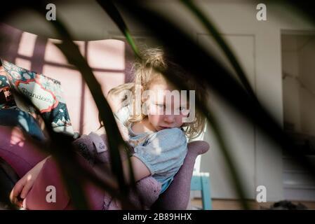 Blick auf ein Kind, das zu Hause auf einem Stuhl sitzt und mit seinem Bruder liest Stockfoto