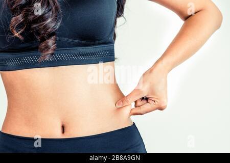 Junge Frau in Sportkleidung ihr Bauch berühren. Diät und Gewichtsverlust Konzept. - Stockfoto