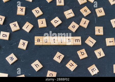 Autismus buchstabierte in Holzklötze mit Buchstaben, die zufällig um das Bild auf dunklem Schieferhintergrund verteilt waren. - Stockfoto