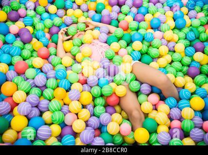 Charmantes Kind im Pool mit bunten Plastikbällen. Mädchen mit rosafarbener Bluse und weißen Shorts - Stockfoto