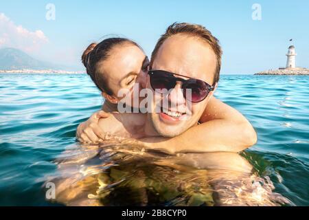 Paar, das selfie im Wasser nimmt, während er im Urlaub im Meer schwimmt. Zwei glückliche Leute im unterhaltsamen Familienurlaub. Romantische Flitterwochen im tropischen Sommer. - Stockfoto