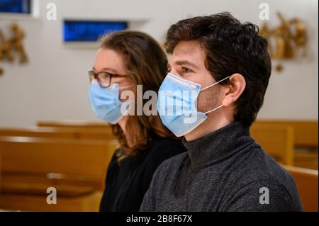 Ein junges Paar in Gesichtsmasken betet während der COVID-19-Pandemie in einer Kirche. Bratislava, Slowakei. - Stockfoto
