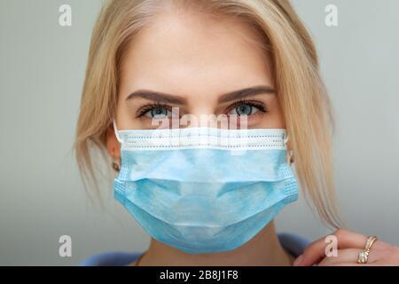 Schöne Frauen in EINER medizinischen Maske. Blonde junge Frau, die eine medizinische Maske trägt, um sie mit den Händen nah beieinander zu verstellen - Stockfoto