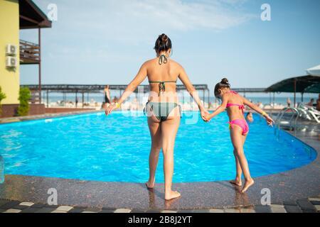 Rückblick ältere Schwester hält die Hand der jüngeren Schwester, bevor sie in den Sommerferien in klares blaues warmes Wasser im Pool springt und sich auf dem Meer entspannt - Stockfoto