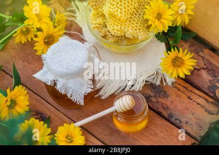 Honig mit Honigabipper auf Holztisch. Organischer Blumenhonig vor verschwommenem Hintergrund mit Blumen - Stockfoto