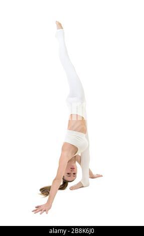 Eine junge Frau in einem weißen Anzug führt akrobatische Elemente und Yoga aus. Studio auf weißem Hintergrund aufgenommen. Isoliertes Bild. - Stockfoto