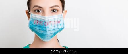 Porträt einer hübschen Frau, die eine medizinische Maske mit einem Virus-Outbreak-Text auf weißem Hintergrund trägt. Coronavirus Konzept. Atemschutz. - Stockfoto