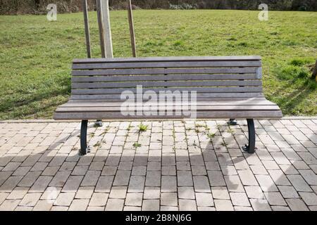 Einsame leere Parkbank auf Kopfsteinpflaster - Stockfoto