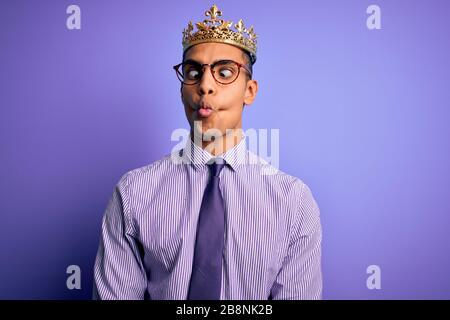 Junger gutaussehender afroamerikanischer Mann mit goldener Königskrone über violettem Hintergrund, der Fisch mit Lippen, verrückter und komischer Geste ins Gesicht zückt. Lustig e - Stockfoto