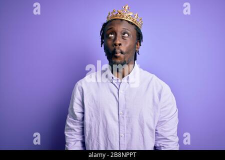 Junger afroamerikanischer Mann mit goldener Königskrone über isoliertem violettem Hintergrund, der Fisch mit Lippen, verrückter und komischer Geste ins Gesicht zückt. Lustig e - Stockfoto