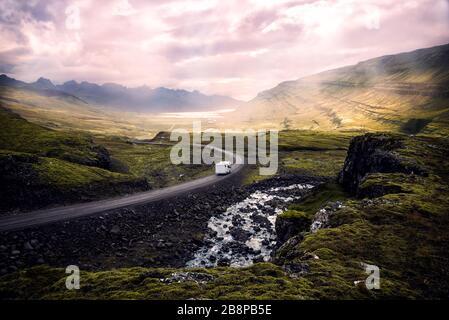 Weißer Camper, der auf der kurvenreichen Bergstraße durch ein wunderschönes, sonnendurchflutes Tal fährt, das von Bergen umgeben ist, Island - Stockfoto