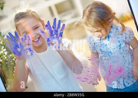 Kinder zeichnen mit Fingerfarben und Händen Fingerabdrücke auf einer Glasscheibe - Stockfoto