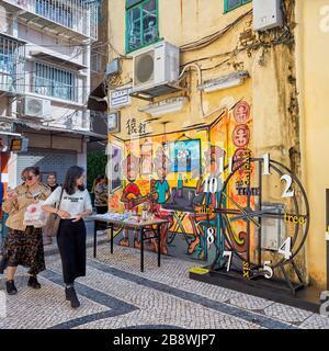 Touristen, die auf der schmalen gepflasterten Straße im historischen Zentrum spazieren gehen. Macau, China.