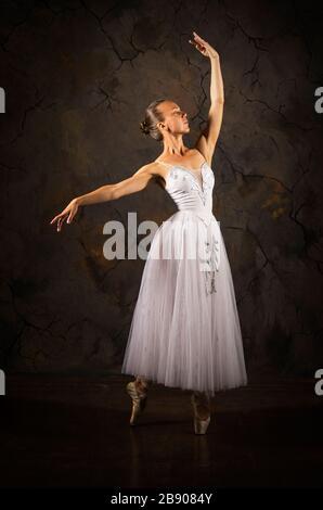 Schlankes Mädchen in einem weißen Korsett tutu tanzenden Ballett. Studioaufnahmen auf dunklem Hintergrund, isolierte Bilder. - Stockfoto