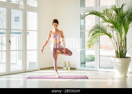 Frau, die Yoga-Balancierung auf einem Bein auf einer Matte in einem modernen, hochmodernen Fitnessstudio mit Topfpflanzen und hohen Fenstern in einer Gesundheits-, Fitness- und Vitalitätsklage praktiziert - Stockfoto