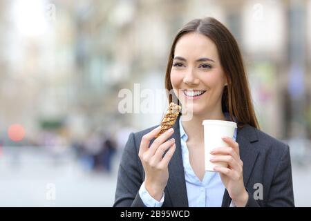 Portrait mit Vorderansicht einer glücklichen Executive-Frau, die eine Getreide-Snack-Bar und einen Kaffee auf der Straße hält - Stockfoto