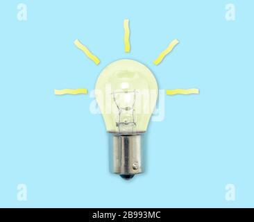 Glühbirne mit Strahlen leuchten, die einen Ideenmoment symbolisieren - Stockfoto