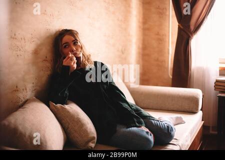 Junge nachdenkliche Frau trinkt Tee, während sie auf dem Sofa im Wohnzimmer zu Hause sitzt - Stockfoto