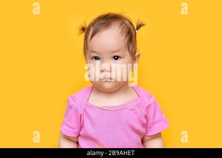 1 Jahr altes verspieltes asiatisch-kaukasisches Mädchen Mixed Race kasachisch und deutsches Mädchen auf gelbem Hintergrund - Stockfoto