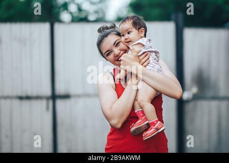Schöne Mutter und Baby im Freien auf dem Hof des Hauses. Beauty Mom und ihr Baby Child ein Jahr alt spielen zusammen im Yard. Mutter und Baby - Stockfoto