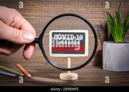 COVID-19-CORONAVIRUS-IMPFSTOFF. Forschung, Untersuchung, Suche und Antwort Konzept. Hand des Mannes, mit Lupe - Stockfoto