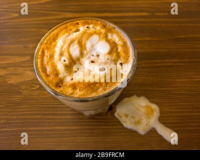 Neben einer Tasse Kaffee auf dem Tisch ist ein sichtbarer Milchschaum mit Adern von Kaffeefarben zu sehen, die Ansicht von oben - Stockfoto