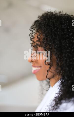 Porträt eines lächelnden schwarzen, lockig behaarten Mädchens.