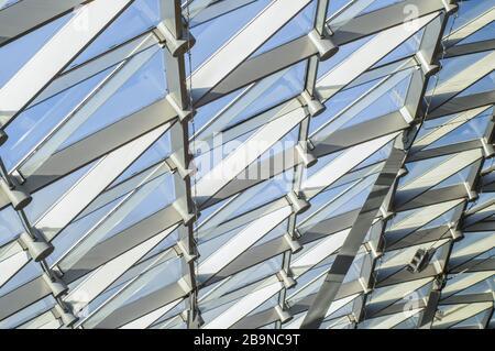 Zaryad-Park im Zentrum Moskaus. Dreiecksmuster aus transparentem Glas eines modernen Daches. Strahlen der Abendsonne, die den Rasen beleuchten. - Stockfoto