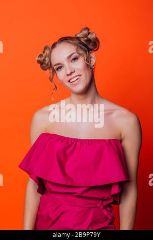 Das Mädchen in einem roten Kleid auf orangefarbenem Hintergrund im Studio. Blondes Mädchen mit zwei Haarknoten, das zur Kamera schaut - Stockfoto