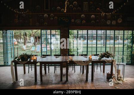 Dekorierte Tische mit Kerzen und Blumenarrangements zum Feiern - Stockfoto
