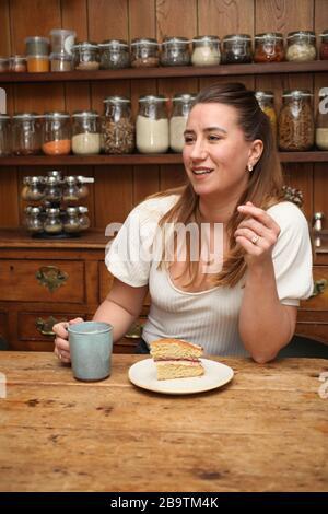 Eine Frau in ihren 30er Jahren plauderte mit einem Becher Kaffee und einem Stück Kuchen - Stockfoto