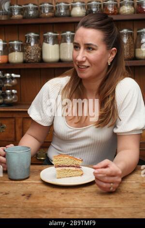 Eine Frau in ihren 30er Jahren mit einem Kaffee und einem Stück Kuchen in ihrer Landküche - Stockfoto